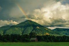 Mooi landschap met hoge heuvels wolken verbazen en een regenboog die achter de heuvel royalty-vrije stock afbeelding