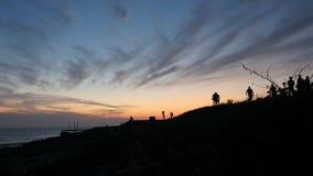 Mooi landschap met kleurrijke zonsondergang en ontspannende en lopende mensen op de kustlijn van Middellandse Zee velen stock videobeelden