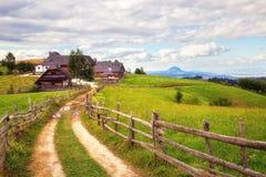 Mooi landschap met landweg die tot een landbouwbedrijf leiden Stock Afbeelding