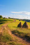 Mooi landschap met weg en hooibergen in Transsylvanië Stock Afbeeldingen