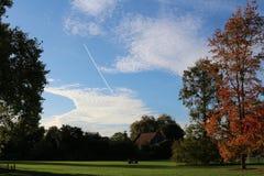 Mooi landschap van park bij de vroege de herfst Afgelegen gelukkige familie die op het gras spelen royalty-vrije stock foto