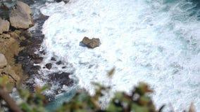 Mooi landschap van steenklippen, oceaangolven en oceanscape Lucht hoogste mening door bladeren Bali, Indonesië langzaam stock video