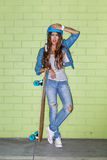 Mooi langharig meisje met een houten longboard dichtbij green Stock Foto