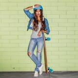 Mooi langharig meisje met een houten longboard dichtbij green Royalty-vrije Stock Foto's