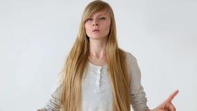 Mooi langharig meisje van Europese verschijning met het blonde haar stellen tegen witte muur emoties - ontkenning en woede stock videobeelden