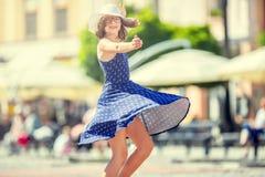 Mooi leuk jong meisje die op de straat van geluk dansen Leuk gelukkig meisje in de zomerkleren die in de zon dansen stock foto