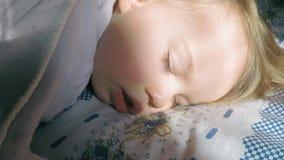 Mooi leuk meisje met blonde haarslaap op het bed en aangestoken door de zon stock videobeelden