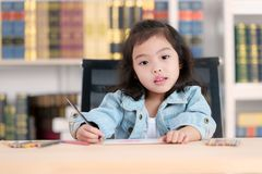 Mooi leuk weinig Aziatisch meisje in jeans die op bureau shirtdrawing Co stock fotografie