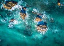 Mooi licht in oceaan die kustrotsen in vloed omringen stock fotografie