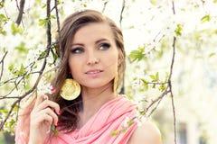 Mooi liefje elegant meisje in een roze jasje dichtbij de boom met witte bloemen met de wind in uw haar Royalty-vrije Stock Afbeelding