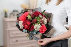 Mooi luxeboeket van gemengde bloemen in vrouwenhand het werk van de bloemist bij een bloemwinkel Een kleine familie stock foto