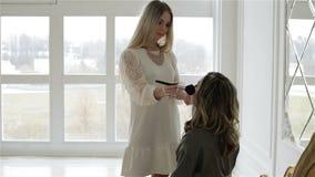 Mooi maak omhoog kunstenaar in witte modieuze kleding werkt met model tegen het grote venster stock videobeelden