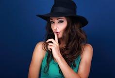 Mooi make-up vrouwelijk model in hoed die geheim teken op blauw tonen stock afbeeldingen