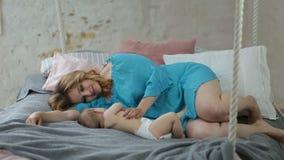 Mooi mamma die haar meisje van de slaapbaby kussen stock footage