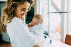 Mooi mamma die haar nieuw houden - geboren zoon en het glimlachen stock foto's