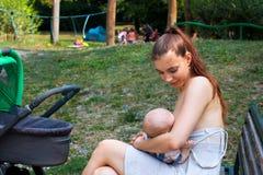 Mooi mamma die haar verzorgen weinig pasgeboren kind in openbare ruimte, baby het voeden tijd terwijl wandelwagengang die buiten, stock fotografie