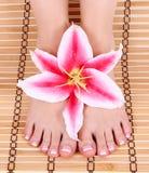 Mooi manicured vrouwelijke naakte voeten met roze leliebloem over bamboemat royalty-vrije stock foto