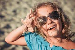 Mooi meisje bij het strand met zeester royalty-vrije stock afbeeldingen