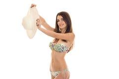 Mooi meisje in bikini die en een hoed glimlachen die houden op witte achtergrond wordt geïsoleerd Royalty-vrije Stock Afbeelding