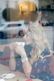 Mooi meisje binnen een koffie met kop van koffie Stock Foto's