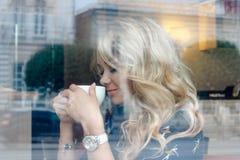 Mooi meisje binnen een koffie met kop van koffie Stock Afbeeldingen
