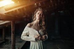 Mooi meisje binnen in witte uitstekende kleding met het krullende haar stellen op de zolder Vrouw in retro kleding Ongerust gemaa stock fotografie