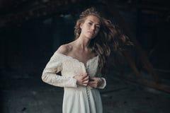 Mooi meisje binnen in witte uitstekende kleding met het krullende haar stellen op de zolder Vrouw in retro kleding Ongerust gemaa royalty-vrije stock foto