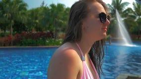 Mooi meisje in blauwe hoed dichtbij pool De Zon van de zomer stock videobeelden