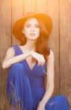 Mooi meisje in blauwe kledingszitting Stock Foto