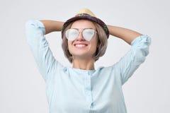 Mooi meisje in blauwe overhemd, hoed en zonnebril die met glimlach stellen stock foto's