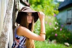 Mooi meisje in bruine hoedenzitting naast oude houten Stock Foto's