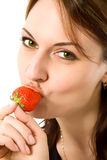 Mooi meisje dat een aardbei eet stock fotografie