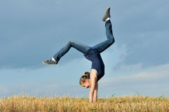 Mooi meisje dat een handstand in een weide doet Royalty-vrije Stock Foto's