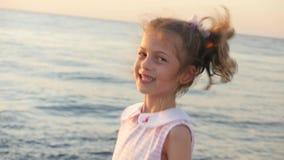 Mooi meisje dat en op de oceaanachtergrond lacht springt stock video