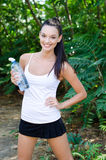Mooi meisje dat houdend een fles water lacht Royalty-vrije Stock Afbeeldingen