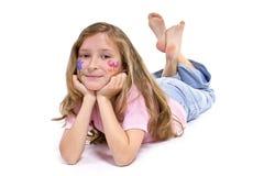 Mooi meisje dat met de samenstelling van de bloemvlinder op de vloer legt stock foto