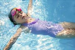 Mooi meisje dat op blauwe pool zwemt Royalty-vrije Stock Foto