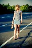 Mooi meisje dat op de weg loopt Stock Afbeeldingen