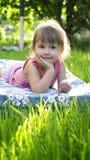 Mooi meisje dat op het gras ligt Stock Foto