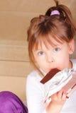 Mooi meisje dat smakelijke chocolade eet Stock Afbeeldingen