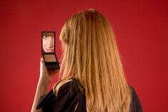 Mooi meisje dat in spiegel kijkt Stock Foto's
