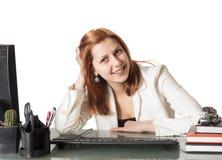 Mooi meisje dat terwijl het zitten bij een bureau in een bureau glimlacht stock afbeelding