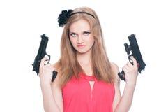 Mooi meisje dat twee kanonnen houdt die op wit worden geïsoleerdo royalty-vrije stock fotografie