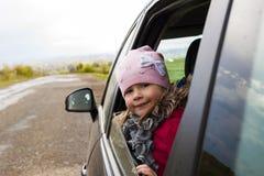 Mooi meisje in de auto die door autoraam kijken Reis Stock Foto
