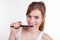 Mooi meisje in de badkamers die zijn tandenglimlach borstelen stock fotografie
