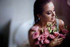 Mooi meisje in de badkamers met vele bloemen stock fotografie