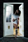 Mooi meisje in de deuropening met een hoofdkussen Royalty-vrije Stock Afbeeldingen