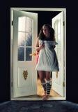 Mooi meisje in de deuropening met een hoofdkussen Stock Foto's