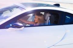 Mooi meisje in de electical witte sportwagen van BMW i8 Stock Afbeelding