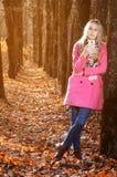 Mooi meisje in de herfst bostribune dichtbij boom en het bekijken telefoon in zonlicht stock afbeeldingen